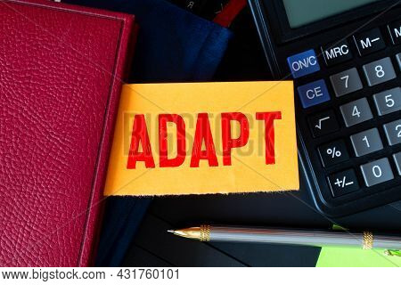 Adapt Word Written On A Yellow Piece Of Paper On A White Background With Office Supplies Lying Nearb