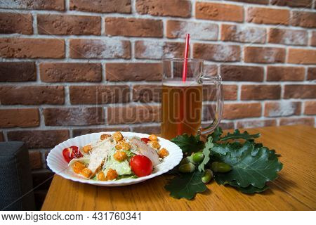 A Pint Of Beer With A Straw And A Caesar Salad. On The Background Of A Brick Wall Bar Pub