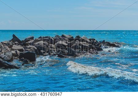 Breakwater Beach Stones On The Sea Coast With Small Waves And Blue Water Against The Background Of T