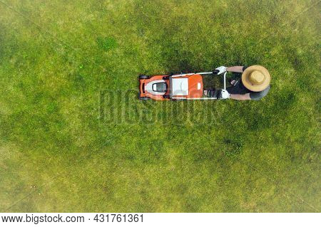 A Young Man Is Mowing A Lawn With A Lawn Mower In His Beautiful Green Floral Summer Garden. A Profes