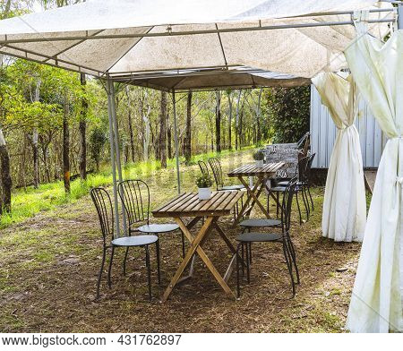 Outdoor Cafe Dining With A Hillside Lean, Rustic Table And Chairs Under A Mildewed Tent