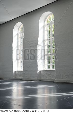 Two Long Arched Windows In A White Painted Brick Wall Indoors In A Large Historic Building, Architec