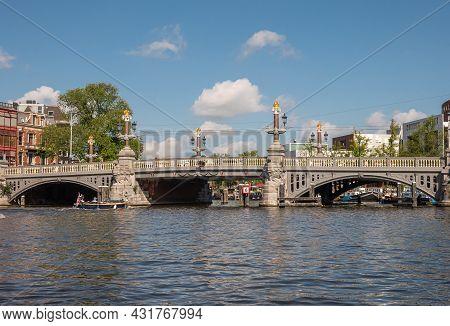 Amsterdam, Netherlands - August 15, 2021: Iconic Blauwbrug (bleu Bridge) Over Wide Amstel River Unde