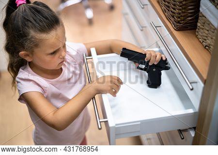 Kid With Gun. Girl Reaching For Pistol In Drawer. Children Safety