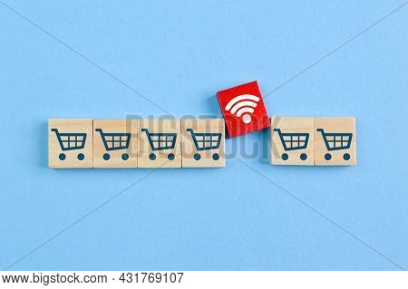 Wooden Block With Shopping Cart And Wifi Symbols. Online Shopping And E-commerce Concept