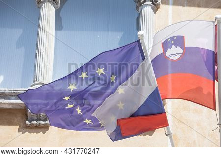 Flags Of The European Union And Slovenia Waiving Together In The Slovenian Capital City, Ljubljana.