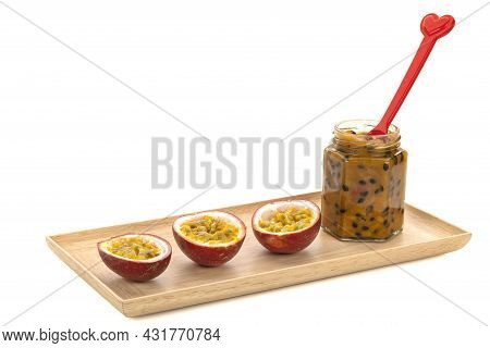 A Bottle Of Passion Fruit Jam With Some Passion Fruit Halved On Wooden Tray.