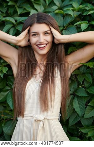 Happy summer time. A beautiful young woman stands by a green hedge and smiles charmingly. Women's beauty.