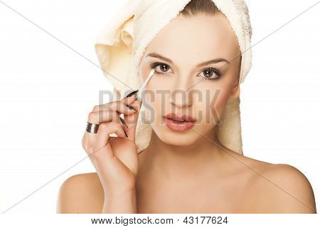 fixing a makeup with a cotton swab