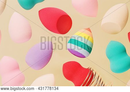 Pattern From Color Cosmetic Beauty Blender Sponges On Beige Background. Flying Red, Pink, Rainbow Co