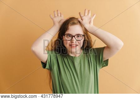 Young happy casual woman with down syndrome standing over beige background grimacing