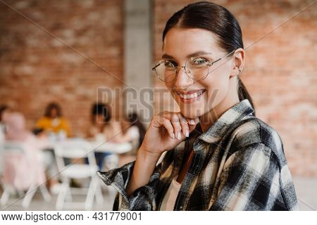 Close up of a happy mid aged white woman standing looking at camera with group of multiethnic women sitting at the table indoors during seminar only for women, feminism concept