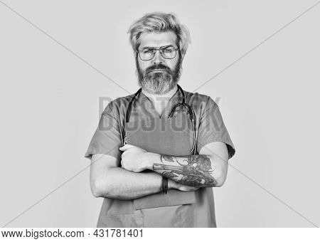 Bad News. Nurse Holding Binder And Wearing Stethoscope. Mature Bearded Male Doctor With A Folder In