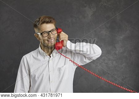 Studio Portrait Of A Happy Young Man Talking On Red Landline Telephone On Gray Background.