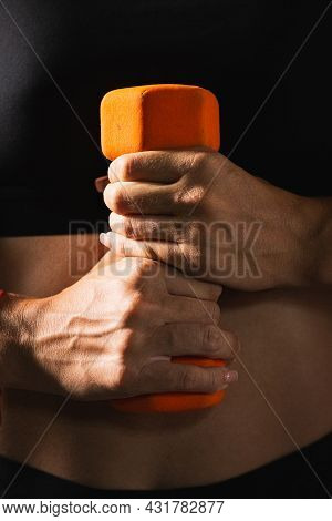 Womens Hands Clasped An Orange Dumbbell And Hold It Along The Torso