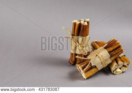 Gray-brown Composition With Dog Treats. Bully Sticks Wrapped In Brown Paper And Tied With Twine. Por