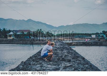 Side View Dad Squatting Hugging Son, Look Far Away. Evening Lake, Mountain Background. Happy Childho