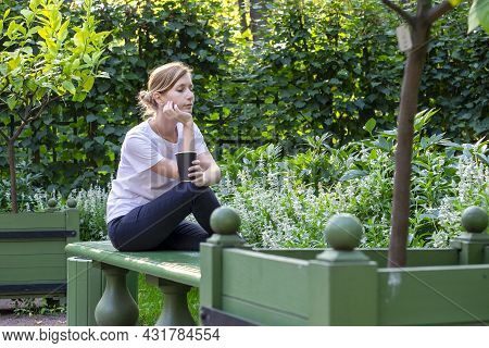 Young Pretty Blonde In White T-shirt Sits On Bench In Park Garden With Her Legs Tucked In And Her He
