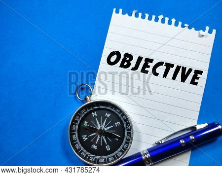Business Concept.text Objective Writing On Notepaper With Pen And Compass On Blue Background.