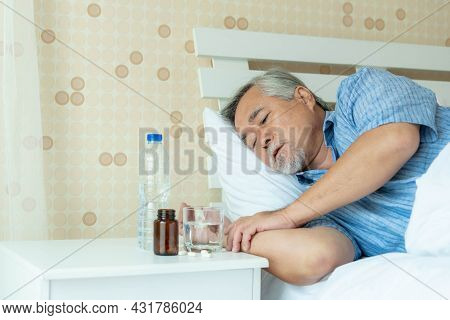 Senior Asian Man ,the Old Man Was Lying Sick In His Bed Alone , Beside His Bed There Was A Table Wit