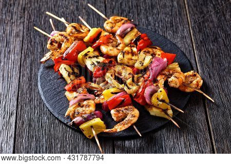 Grilled Shrimp Kabobs With Charred Red Onion, Sweet Pepper And Pineapple On A Black Stone Platter