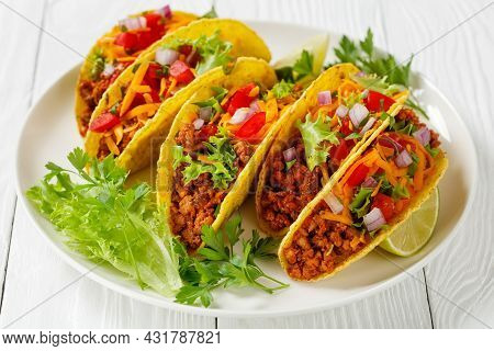 Ground Beef Tacos With Shredded Cheddar Cheese, Fresh Lettuce, Tomato, Onion On A White Plate With L
