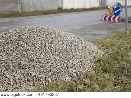 A Pile Of Gravel For Pothole Repair And Warning Signs, Focus In The Foreground