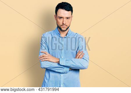 Hispanic man with beard wearing casual business shirt skeptic and nervous, disapproving expression on face with crossed arms. negative person.