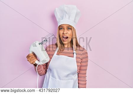 Beautiful hispanic woman holding pastry blender electric mixer angry and mad screaming frustrated and furious, shouting with anger. rage and aggressive concept.