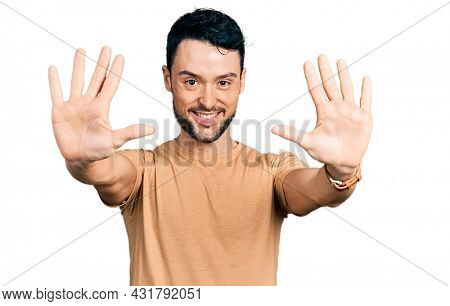Hispanic man with beard wearing casual t shirt showing and pointing up with fingers number ten while smiling confident and happy.