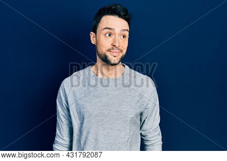 Young hispanic man wearing casual clothes smiling looking to the side and staring away thinking.