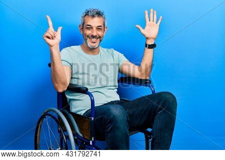 Handsome middle age man with grey hair sitting on wheelchair showing and pointing up with fingers number seven while smiling confident and happy.