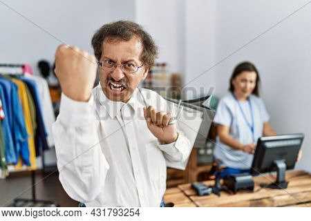 Southeast asian man wearing holding shopping bags annoyed and frustrated shouting with anger, yelling crazy with anger and hand raised