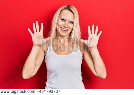Beautiful caucasian blonde woman wearing casual white t shirt showing and pointing up with fingers number ten while smiling confident and happy.