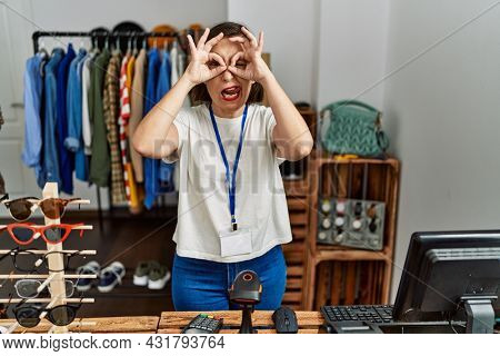 Beautiful middle age hispanic woman working as manager at retail boutique doing ok gesture like binoculars sticking tongue out, eyes looking through fingers. crazy expression.