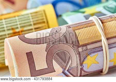 Fifty Euro Bill Rolled Up As A Tubule Lies On The Background Of Euro Bills. Fifty Euro Banknote Deta