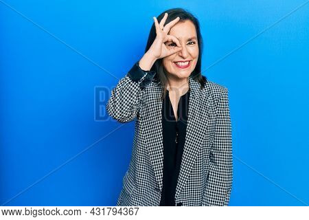 Middle age hispanic woman wearing business clothes doing ok gesture with hand smiling, eye looking through fingers with happy face.