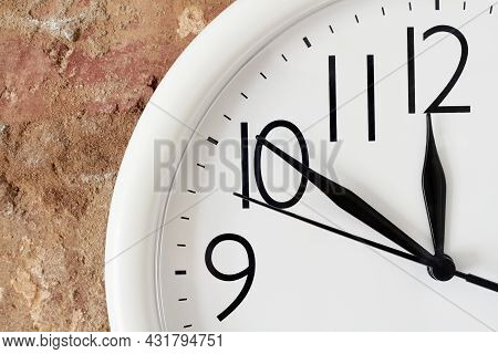 Lunch Time Concept. A Part Of White Round Analog Clock Face Against The Background Of A Red Brick Wa