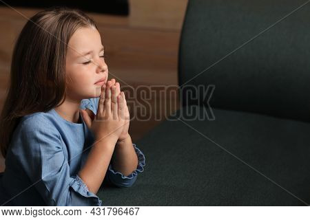 Cute Little Girl With Hands Clasped Together Praying Indoors. Space For Text