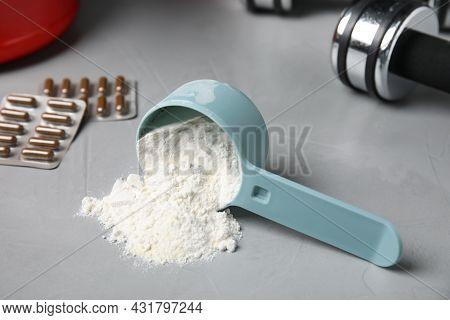Measuring Scoop Of Amino Acids Powder On Light Grey Table