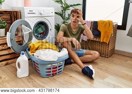 Young caucasian man putting dirty laundry into washing machine doing ok gesture shocked with surprised face, eye looking through fingers. unbelieving expression.
