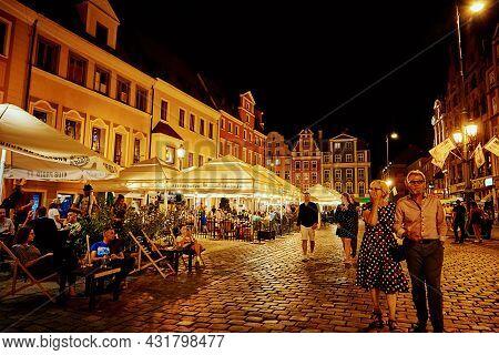 Night City Life. Tourists Walks At Night City Street. Wroclaw, Poland - August 14, 2021