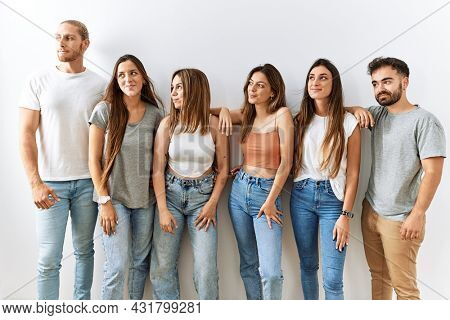 Group of young friends standing together over isolated background smiling looking to the side and staring away thinking.
