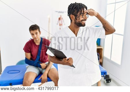 Young hispanic man working at pain recovery clinic with a man with broken arm very happy and smiling looking far away with hand over head. searching concept.