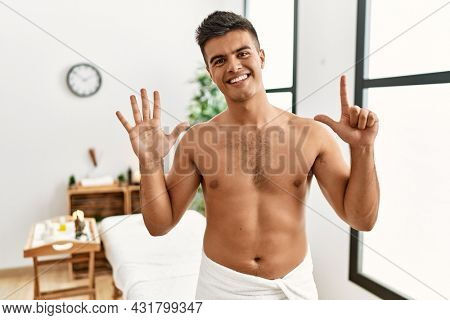 Young hispanic man standing shirtless at spa center showing and pointing up with fingers number seven while smiling confident and happy.