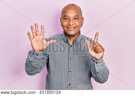 Middle age latin man wearing casual clothes showing and pointing up with fingers number seven while smiling confident and happy.