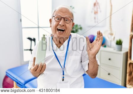 Senior physiotherapy man holding massage body lotion screaming proud, celebrating victory and success very excited with raised arms