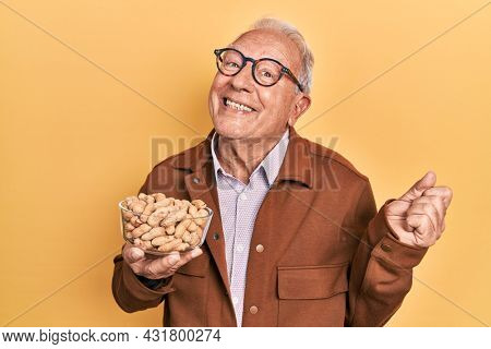 Senior man with grey hair holding peanuts screaming proud, celebrating victory and success very excited with raised arm