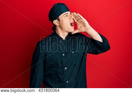 Handsome young man wearing professional cook uniform and hat shouting and screaming loud to side with hand on mouth. communication concept.