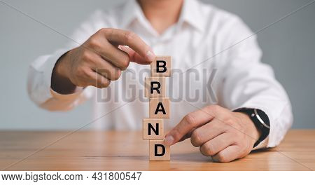 Businessman Building Wood Cube Block With Word Brand On Table. Growth Business And Brand Building Fo